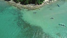 Luftbrummenansicht von traditionellen Philippinen-Booten verankert in der Bucht mit Wasser des freien Raumes und des Türkises tro stock video footage