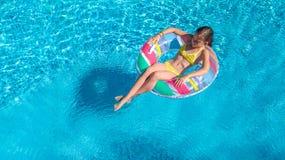 Luftbrummenansicht wenigen Mädchens im Swimmingpool von oben genanntem, Kinderschwimmen auf aufblasbarem Ringdonut, Kind hat Spaß lizenzfreies stockfoto