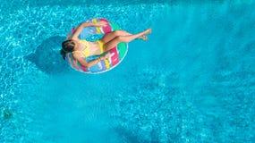Luftbrummenansicht wenigen Mädchens im Swimmingpool von oben genanntem, Kinderschwimmen auf aufblasbarem Ringdonut, Kind hat Spaß lizenzfreie stockbilder