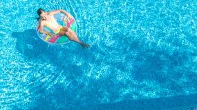 Luftbrummenansicht wenigen Mädchens im Swimmingpool von oben genanntem, Kinderschwimmen auf aufblasbarem Ringdonut, Kind hat Spaß stockfotos