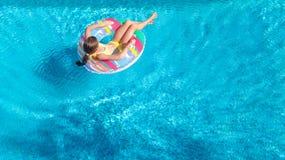 Luftbrummenansicht wenigen Mädchens im Swimmingpool von oben genanntem, Kinderschwimmen auf aufblasbarem Ringdonut, Kind hat Spaß stockfotografie