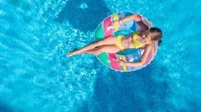 Luftbrummenansicht wenigen Mädchens im Swimmingpool von oben genanntem, Kinderschwimmen auf aufblasbarem Ringdonut, Kind hat Spaß lizenzfreies stockbild