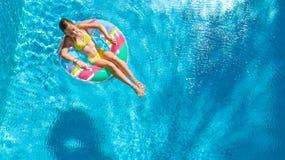 Luftbrummenansicht wenigen Mädchens im Swimmingpool von oben genanntem, Kinderschwimmen auf aufblasbarem Ringdonut, Kind hat Spaß stockbild