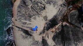 Luftbrummenansichtfrau im blauen Kleidertanzen auf Fusions-Hintergrundmeer der Klippe Stammes-, Bungalow stock footage