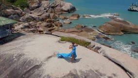 Luftbrummenansichtfrau im blauen Kleidertanzen auf Fusions-Hintergrundmeer der Klippe Stammes-, Bungalow stock video