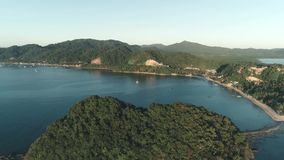 Luftbrummenflug über der Insel bedeckt mit tropischem Wald auf Sonnenuntergangzeit Tropische Paradiesbucht mit Booten auf stock footage