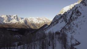 Luftbrummenflug establisher über gefrorenem See mit Skifahrer und schneebedeckter Waldwinterschnee in der Gebirgsnatur draußen stock footage
