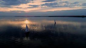 Luftbrummengesamtlänge der ruhigen Szene mit den Yachten, die am ruhigen Wasser an der Dämmerung kreuzen stock video