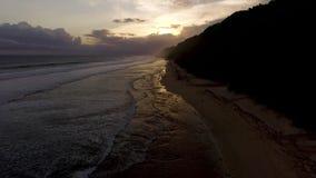 Luftbrummengesamtlänge von den Meereswogen, die vor dem Ufer auf Sonnenuntergang brechen Bali, Indonesien stock video footage