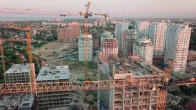 Luftbrummenschuß Bau von hohen Gebäuden im sich entwickelnden Bereich von einer Großstadt Sonnenuntergangschuß Abfall unten stock video footage