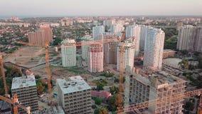 Luftbrummenschuß Bau von hohen Gebäuden im sich entwickelnden Bereich von einer Großstadt Sonnenuntergangschuß Spanne oben stock video