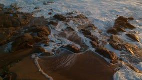 Luftbrummenschuß bei dem Sonnenuntergang, der schnell über Felsen als Wasserströme zum Ozean fliegt und Vögel fliegen unten stock video
