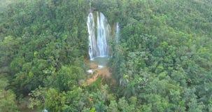 Luftbrummenvogel ` s Augen-Ansichtvideo auf Palmenwald mit einem Wasserfall in der Mitte tropisches Paradiespazifik-Atoll stock footage