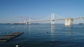 Luftdrohnenfliegen, Rückzug herein von ruhigem, blauem Meer, Seto-Brücke stock footage