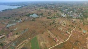 Luftfliege über Draufsicht des Reisfeldes und -dorfs in landeinwärts Thailand, beweglicher Kameraansichtschuß, Gesamtlänge 4K der stock video footage