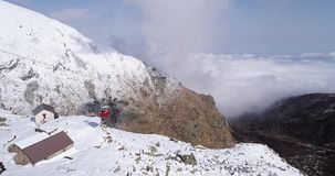 Luftfliegen über schneebedecktem Gebirgsrückental mit Wolken, rotes Drahtseilbahn anhebendes establisher Des im Freien alpines wi stock video footage