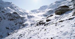 Luftfliegen, das sich über nahes establisher Häuschen des schneebedeckten Gebirgsrückentales zurückbewegt Des im Freien alpine wi stock footage