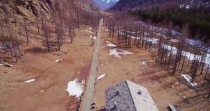 Luftfliegen, das sich weg über nahes Häuschen des Weges im gelbem Gebirgstal und in Waldholzfall establisher zurückbewegt stock video