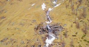Luftfliegen, das sich weg von Wasserfall in gelbem Gebirgsseiten-Fall establisher zurückbewegt Des im Freien alpines wildes Schne stock video