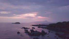 Luftfliegen des Betäubungssonnenuntergangs 4k durch Laub über blauem Meer und purpurroten Wolken stock video