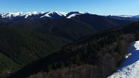 Luftflug über Wald und Hügeln mit dem Gebirgszug, landend stock footage