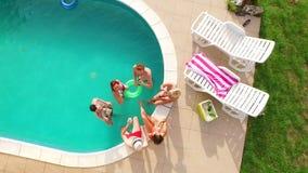 Luftflug: Gruppe junge Freunde, die heraus zusammen durch das Pool mit Getränken hängen stock video