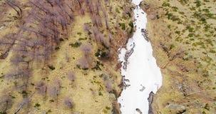 Luftflugobenliegender Überwasserfallnebenfluß in gelbem Gebirgstal-Fall establisher Des im Freien wildes scape Natur Schnees here stock video
