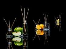 Luftfresheners i ett exponeringsglas skorrar med pinnar och citronen, det gröna äpplet och apelsinen med reflexion som isoleras p Arkivfoton