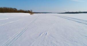Luftgesamtlänge der Winterlandschaft von einem gefrorenen Fluss mit einem Wald und der Ansicht der Stadt mit Fabriken Spuren von stock video footage