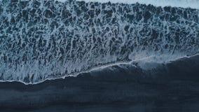 Luftgesamtlänge des Schwarzwassers, schlagende schäumende Wellen, schwarzer Sandstrand auf Bali stock video footage