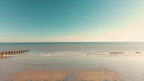 Luftgesamtlänge eines Brummens, das in Richtung zum Meer auf einem englischen Strand bei Sonnenaufgang sich bewegt stock video footage