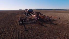 Luftgesamtlänge 4k eines modernen Traktors, der trockenes Feld, Land für das Säen vorbereitend pflügt stock video