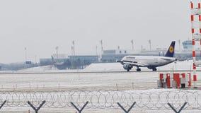 Lufthansa Airbus apenas que aterriza en el aeropuerto de Munich, MUC, nieve almacen de metraje de vídeo