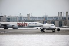 Lufthansa Airbus A340-600 D-AIHZ taxiing in Munich Airport, winter time, FC Bayern livery. Lufthansa Airbus A340-600 D-AIHZ doing taxi in Munich Airport, MUC royalty free stock photo
