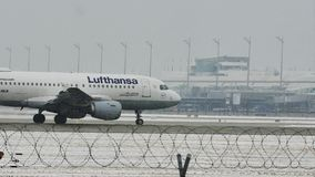 Lufthansa Airbus A319-100 D-AILB in Munich Airport, snow. Lufthansa jet taxiing in Munich Airport, Germany, winter time with snow on runway. Flughafen München stock footage