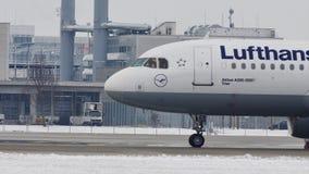 Lufthansa Airbus A320-200 D-AIZA che passa pista nevosa, aeroporto di Monaco di Baviera archivi video