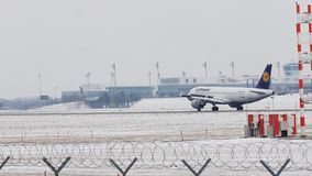 Lufthansa Airbus just landing on Munich Airport, MUC, snow. Lufthansa Airbus jet landing on snowy runway in Muenchen Flughafen, Germany stock video footage