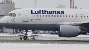 Lufthansa Airbus A320-200 que mueve encendido la pista nevosa, aeropuerto de Munich almacen de metraje de vídeo
