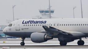 Lufthansa Airbus A320-200 que saca de la pista nevosa, Munich metrajes