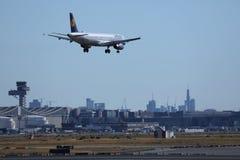 Lufthansa aplana a aterrissagem no aeroporto de Francoforte, FRA, construções no fundo imagem de stock