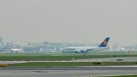 Lufthansa aplana taxiing no aeroporto de Francoforte, FRA, construções no fundo