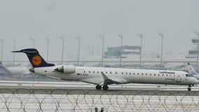 "Lufthansa CityLine Bombardier CRJ-900 D-ACKH. Lufthansa jet takes off from Munich Airport, Germany, winter time with snow on runway. Flughafen München "" stock video footage"