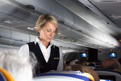 Lufthansa flight attendant. Munich, Germany - July 16, 2017:  A female flight attendant is listening a request from a passenger sitting in the economy class of Stock Image