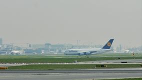 Lufthansa plane taxiing in Frankfurt Airport, FRA, buildings on background. Lufthansa in Frankfurt Airport, FRA, Germany stock footage