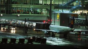 Lufthansa plane at terminal gate, night view, Munich. Lufthansa jet in Munich Airport, night view. Plane at terminal gate waiting its passengers stock video
