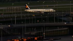 Lufthansa plane doing taxi in Munich Airport, evening light. Lufthansa jet taxiing in Munich Airport, MUC, spring. Roads and traffic near the airport stock footage