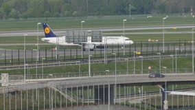 Lufthansa plane doing taxi in Munich Airport, spring. Lufthansa jet taxiing in Munich Airport, Germany, spring time with snow on runway. Flughafen München stock video footage