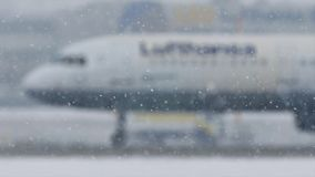 Lufthansa plane on heavy snow, low visibility, close-up view. Lufthansa jet doing taxi in Munich Airport, Germany, winter time with snow on runway. Flughafen M stock footage