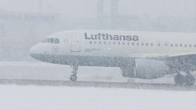 Lufthansa plane on heavy snow, low visibility, close-up view. Lufthansa jet doing taxi in Munich Airport, Germany, winter time with snow on runway. Flughafen M stock video footage
