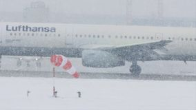 Lufthansa plane on heavy snow, low visibility, close-up view. Lufthansa jet doing taxi in Munich Airport, Germany, winter time with snow on runway. Flughafen M stock video